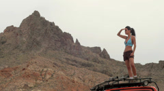 An Adventure Girl Stands on Land Rover in Wilderness Stock Footage