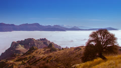 Timelapse landscape with tree and of dense layer of fog among mountain peaks Stock Footage