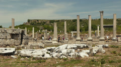 Tourist walking along a row of columns in an ancient city Perge in southern Stock Footage