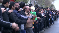 Ashura in Iran, father holds child in procession, sombre parade - stock footage