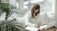 Attractive girl wearing headset sitting on floor by window writing in notebook - stock footage