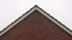 Falling snow with a triangular roof background Stock Footage