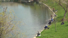 Fishermen Fishing on Edge of a Lake, People Relaxing on Meadow in Park in Spring Stock Footage