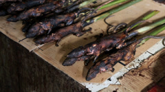 Skewered forest rat for sale in market Stock Footage