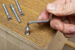 tightening the screws by hand when assembling furniture - stock photo