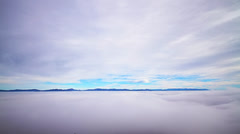 Timelapse scenery with clouds, dense layer of fog and mountain peaks - stock footage