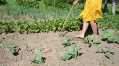 Barefoot girl in yellow dress grub weeds with hoe in garden Stock Footage