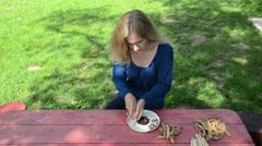 Pretty gardener girl unhusk decorative beans to white dish Stock Footage