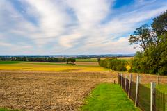 fence and view of farm fields in rural lancaster county, pennsylvania. - stock photo