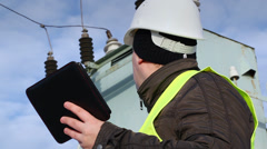 Worker with tablet PC near transformer  - stock footage