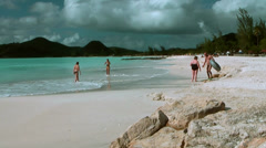 Antigua Jolly Beach 089, wide view, green hills, a few people far away Stock Footage