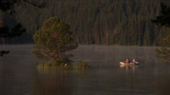 Two fishermen in a boat in the middle of the lake and huge pines Stock Footage