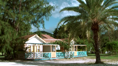 Antigua Jolly Beach 099, beach huts between exotic trees Stock Footage