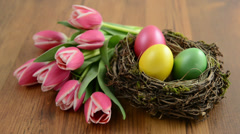 Rack focus of Easter decoration with eggs, tulips and host Stock Footage