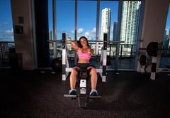young brunette woman exercising and stretching in a gym - stock photo