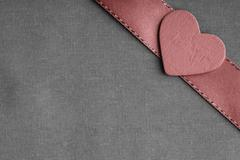 Stock Photo of red wooden decorative heart on grey gray cloth background.
