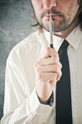 businessman thinking with pencil in his mouth - stock photo