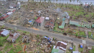 Aerial following a road on the coast through destroyed villages Stock Footage