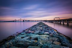 long exposure of a jetty and the chesapeake bay bridge, from sandy point stat - stock photo