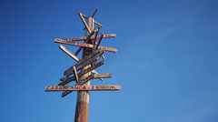 Wooden traffic sign pointing to various cities and directions - stock footage