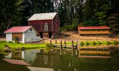 reflection of barn and house in a small pond in rural york county, pennsylvan - stock photo
