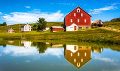 reflection of house and barn in a small pond, in rural york county, pennsylva - stock photo