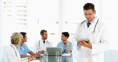 Stock Video Footage of Thoughtful doctor using tablet with staff talking behind him