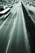Highway with lots of cars. Green tint, high contrast and motion blur to rise spe - stock photo