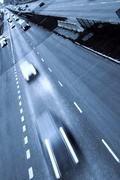 Highway with lots of cars. Blue tint, high contrast and motion blur to rise spee - stock photo