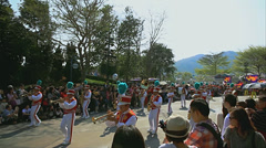Brightly dressed brass band playing and performing in the street Stock Footage