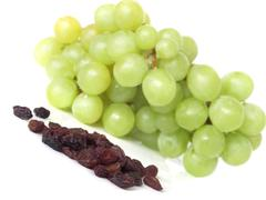 Isolated yellow grape cluster and raisins on white background - stock photo