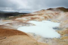 toxic pool and steam raising from it near krafla, iceland - stock photo