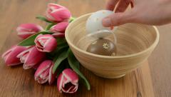 Laying easter eggs in a cup with bunch of tulips around. Stock Footage