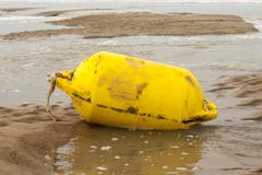 Yellow sea buoy at the beach offshore Stock Photos