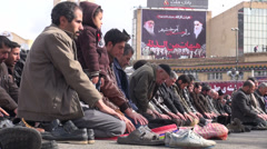 Iran, public prayer, Imam Khomeini billboard, Islam, muslim men Stock Footage