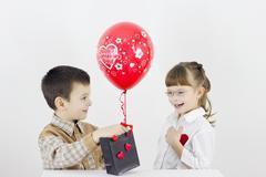 Stock Photo of boy gives a girl a gift, balloon