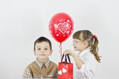 Girl with glasses gives a gift to the boy Stock Photos