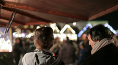 Young couple watching a winter market at night Stock Footage