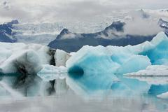 Icebergs of different colors reflecting in still water, jokulsarlon, iceland Stock Photos
