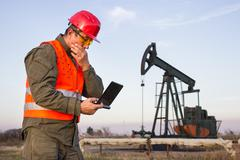Man on the oil rig holds laptop and thinking Stock Photos