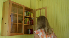 Girl put glass pots full of canned pickled food product to rack Stock Footage