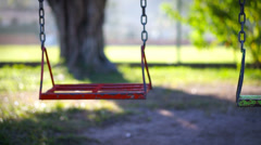 Empty swing in a children's playground - stock footage
