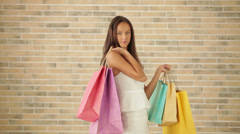 Excited young woman posing with shopping bags looking at camera and smiling - stock footage
