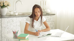 Pretty girl sitting at table with laptop writing in workbook looking at camera Stock Footage