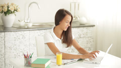 Pretty girl sitting at table using laptop drinking juice and smiling Stock Footage