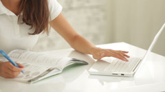 Charming girl sitting at table writing in workbook using laptop looking  Stock Footage