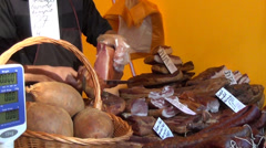 Vendor cuts red piece smoked ham near the scales farmer market Stock Footage