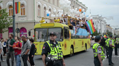 Bus drive street town gay parade members white balloons flags Stock Footage