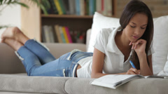 Cheerful girl lying on sofa writing in workbook looking at camera and smiling Stock Footage