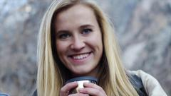 Pretty Blonde Teen Sips A Hot Drink And Smiles - stock footage